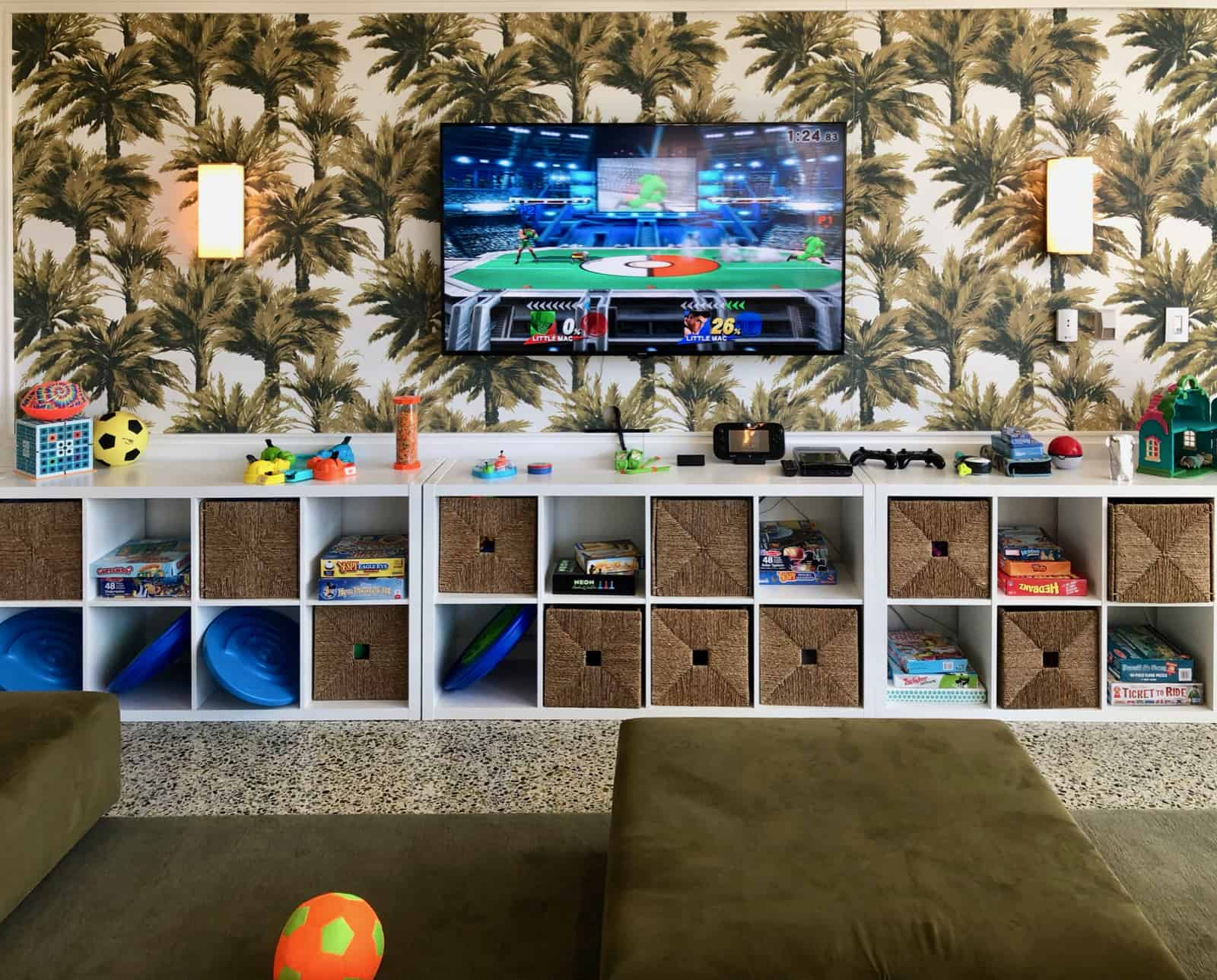 A closeup shot of one of the walls at the Surf Club Kids Club with a shelf filled with toys, and a tv for video games.