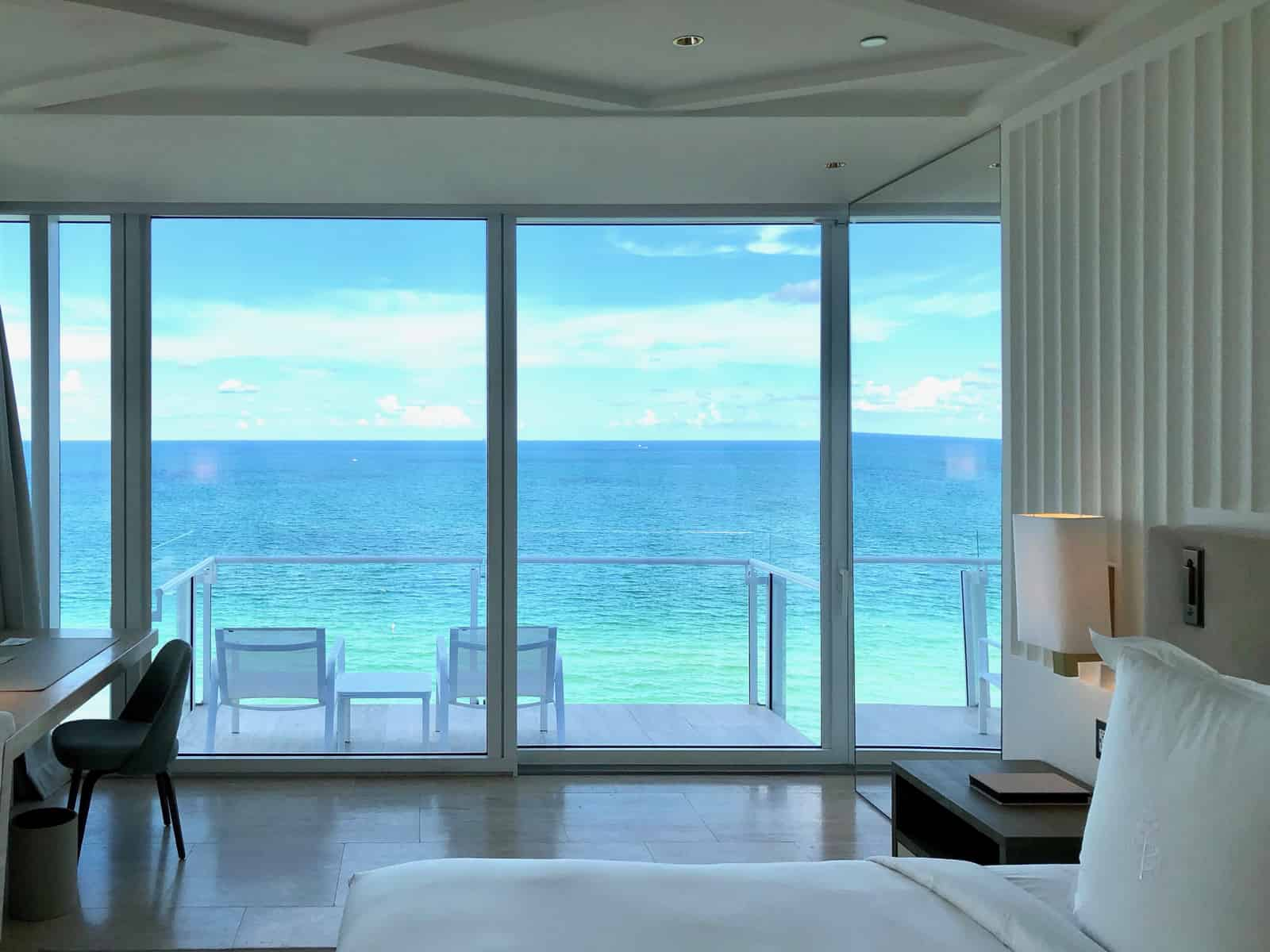 A view of a room at the Four Seasons Surf Club looking out on a balcony and the ocean.